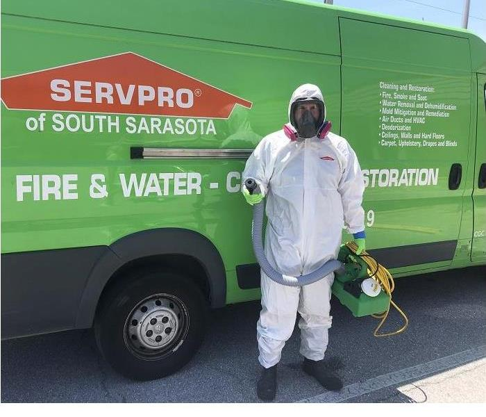 Male employee in PPE in front of a green SERVPRO van