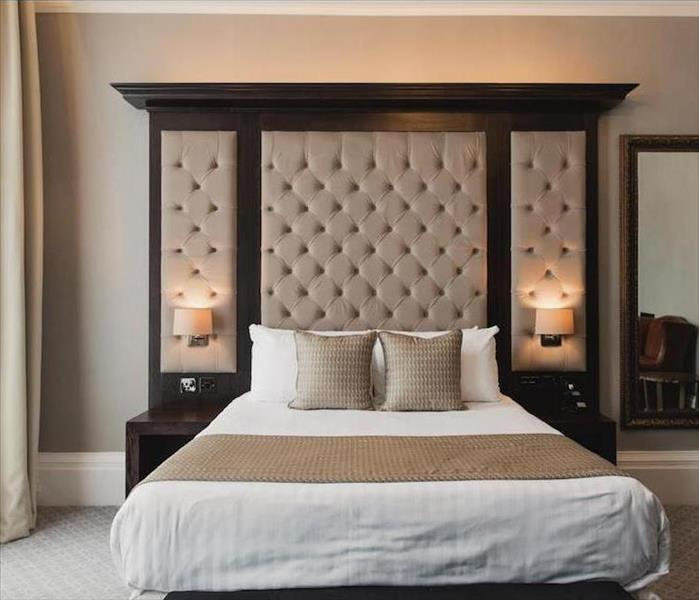 luxury hotel room with bed that has large headboard