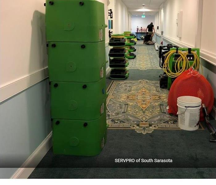 Commercial building hallway with SERVPRO drying equipment stacked on sides near walls after completing job