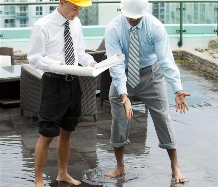 Two men standing in water on top of a building, neither men are wearing shoes and have their pants rolled up.