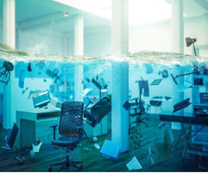 Office with chairs and desks floating in a pool of water