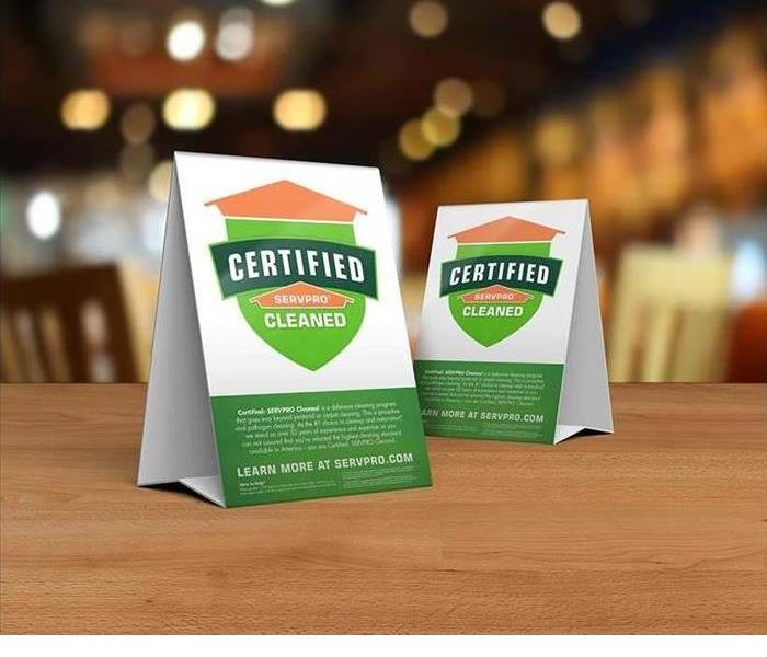 Table tent signs describing the Certified: SERVPRO Cleaned program on top of a wooden table. Certified: SERVPRO Cleaned