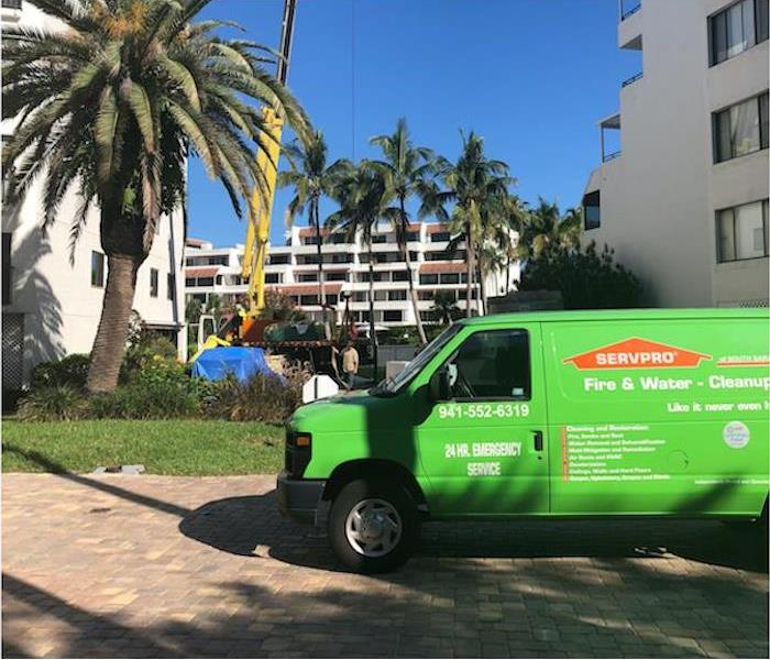 SERVPRO van on a brick road in front of white buildings and palm trees