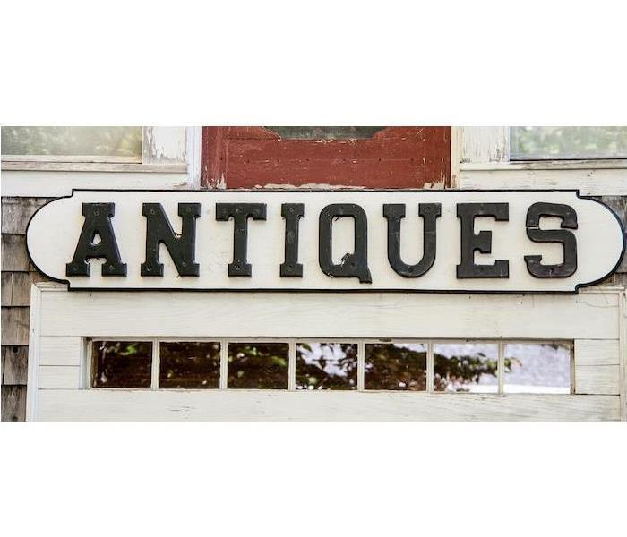 Cream wood sign that says Antiques in black
