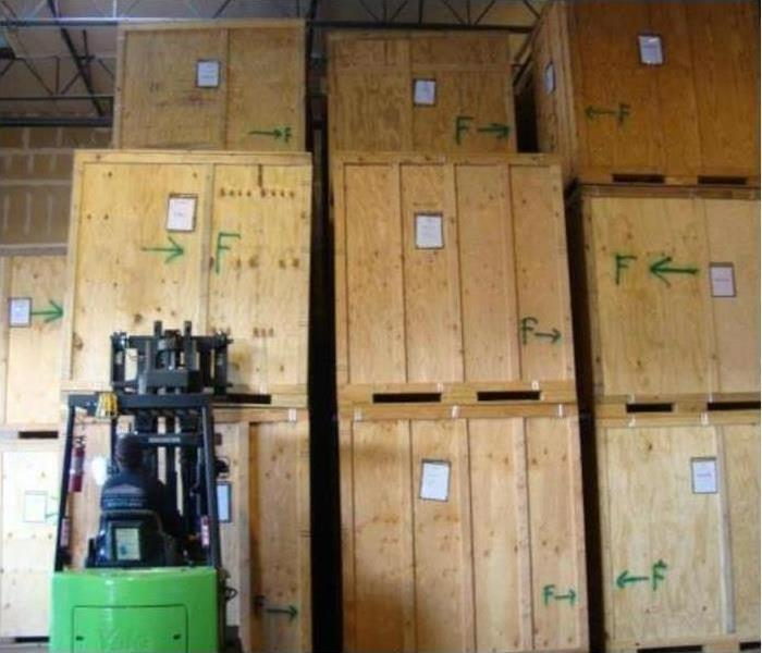 wooden crates stacked in warehouse with forklift in foreground
