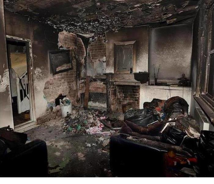Heavily fire damaged room with burnt walls and furniture