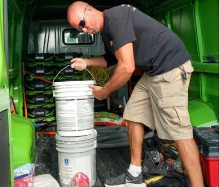 SERVPRO Tech loading restoration equipment into vehicle